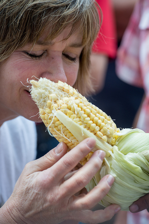 Woman smelling and tasting fresh corn in the Curacavi Valley at a produce farm in Chile