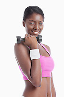Portrait of happy young woman holding dumbbell over white background