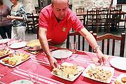 Pedro Monje serves food at a table in the Txoko Uri-Zarra in Bilbao, Spain.