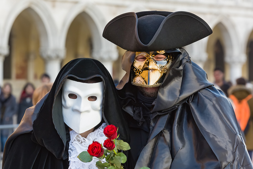 A couple are seen walking alongside the Doge's palace in St Mark's square Venice. they are wearing the traditional Bauta mask and cape, also can be seen the accompanying tricorn hat.