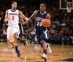 Xavier guard/forward C.J. Anderson (20) dribbles past Virginia guard Mustapha Farrakhan (2).  The #22 ranked Xavier Musketeers defeated the Virginia Cavaliers 84-70 at the John Paul Jones Arena on the Grounds of the University of Virginia in Charlottesville, VA on January 3, 2009.