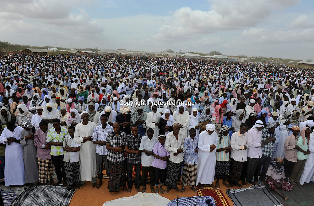 Somali refugees stand in prayer during celebrations of the Eid ul Fitr to mark the end of Ramadan in the Ifo marketplace at Kenya's Dadaab Refugee Camp, situated northeast of the capital Nairobi near the Somali border, August 2011.