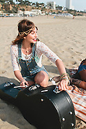 Pretty woman opening a guitar case at the beach.