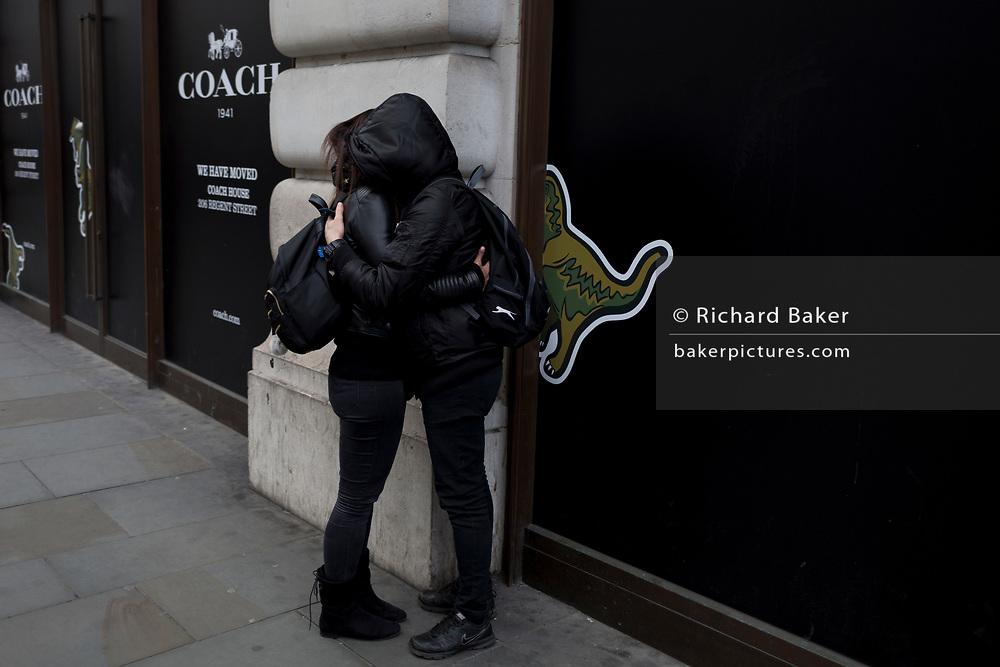 A couple wearing black hoodies hug on Regent Street, on 21st March 2017, in London, England.