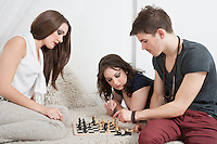 Young friends playing chess on sofa