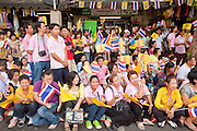 05 MAY 2010 - BANGKOK, THAILAND: People on the street in front of the Grand Palace in Bangkok wait for Thai King Bhumibol Adulyade, Wednesday, May 5. Wednesday was Coronation Day in Thailand, marking the 60th anniversary of the coronation of Thai King Bhumibol Adulyade, also known as Rama IX. He is the world's longest serving current head of state and the longest reigning monarch in Thai history. He has reigned since June 9, 1946 and his coronation was on May 5, 1950, after he finished his studies. The King is revered by the Thai people. Thousands lined the streets around the Grand Palace hoping to catch a glimpse of the King as his motorcade pulled into the palace. The King has been hospitalized since September 2009, making only infrequent trips out of the hospital for official functions, like today's ceremonies.   PHOTO BY JACK KURTZ
