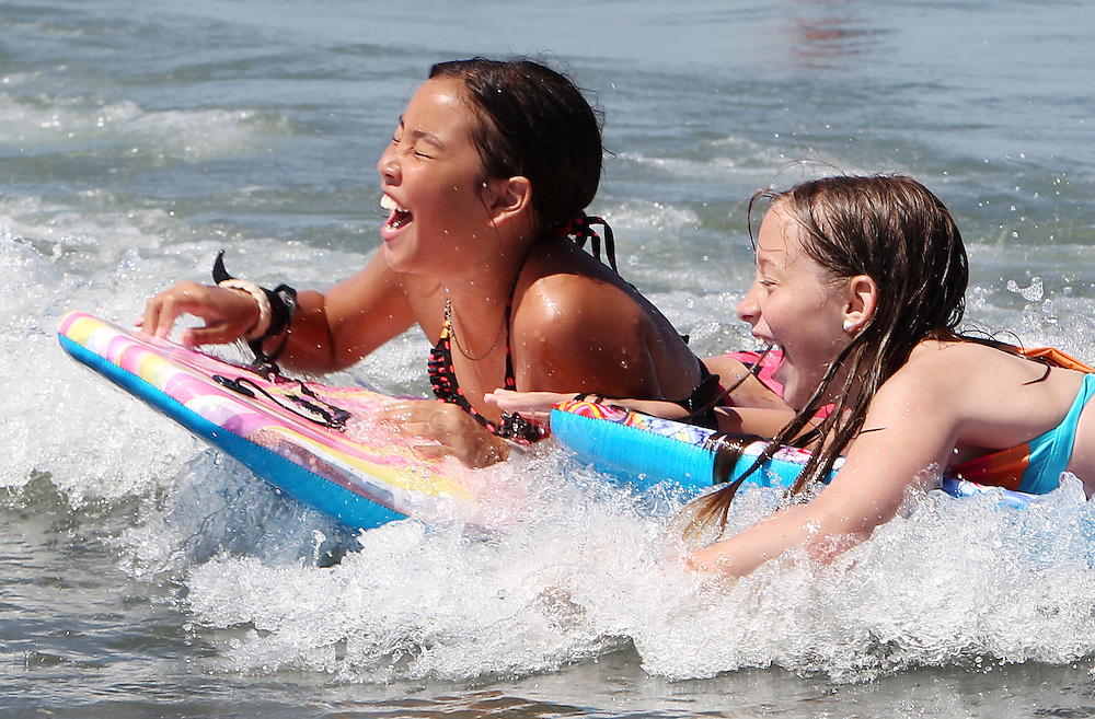 (071011  Hull, MA) Krista Hickey, 10, of Dorchester, left, and Laina Hall, 10, of Braintree, ride the waves at Nantasket Beach, Sunday,  July 10, 2011.  Staff photo by Angela Rowlings.