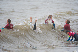 © Licensed to London News Pictures. 16/09/2018. Aberystwyth, UK. Young members of the local life saving club training in the waves along the seafront in Aberystwyth, Wales on a wet and dreary September Sunday afternoon. The west of the UK is bracing itself for the impact of Storm Helene, which is predicted to strike overnight on Monday, with winds gusting up to 70mph in exposed areas. Photo Credit: Keith Morris/LNP
