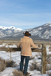 back of a cowboy in Winter looking towards a mountain range