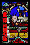 Mary of Egypt worships the True Cross in a church, from the stained glass window of St Mary of Egypt, 1215-25, in bay 21, in the ambulatory of Bourges Cathedral or the Cathedrale Saint-Etienne de Bourges, built 1195-1230 in French Gothic style and consecrated in 1324, in Bourges, Centre-Val de Loire, France. 22 of the original 25 medieval stained glass windows of the ambulatory have survived. The cathedral is listed as a UNESCO World Heritage Site. Picture by Manuel Cohen