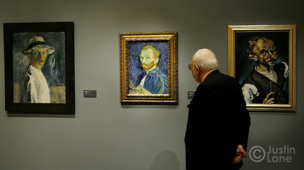 A man looks over three self portraits by, from left, Ludwig Weidner, Vincent van Gogh and Emil Nolde at an exhibit exploring the influence of van Gogh on German and Austrian Expressionism at the Neue Galerie in New York, New York on Wednesday 21 March 2007. The exhibit, which features over 80 major paintings, will be open until 02 July 2007.