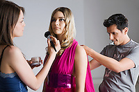 Designer and Makeup Artist Preparing Model for Photo Shoot