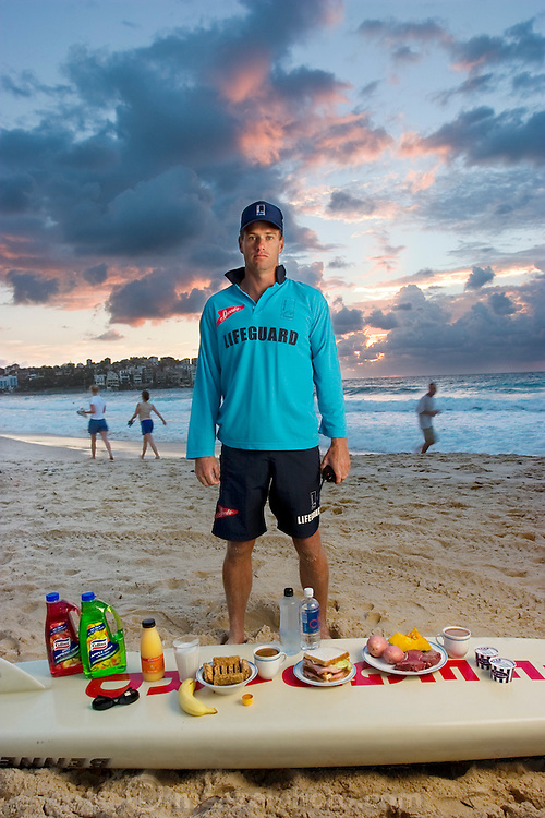 Bruce Hopkins, a Bondi Beach lifeguard, with his typical day's worth of food in Sydney, New South Whales, Australia.  (From the book What I Eat: Around the World in 80 Diets.)  The caloric value of his day's worth of food on a typical day in the month of February was 3700 kcals. He is 35 years of age;  6 feet tall, and 180 pounds. Hopkins eats moderately, rarely?if ever?eats fast food, and drinks alcohol only when he and his wife go to dinner with friends. MODEL RELEASED.