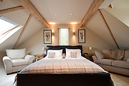 Upstairs bedroom interior with low sloping ceilings, a double bed and comfy couches in a neutral beige