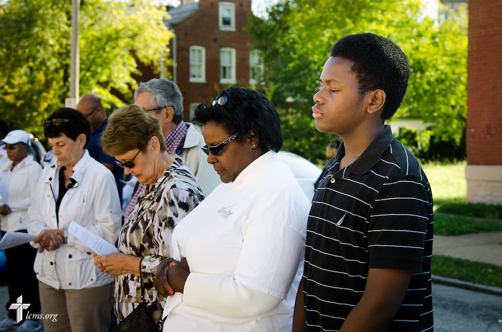 Anna Paul, her son, Alexander, and other attendees pray before the the LCMS Prayer & Praise Walk on Friday, Oct. 17, 2014, in the College Hill neighborhood of St. Louis. Anna is a project director for LCMS National Housing Support Corporation (NHSC). LCMS Communications/Frank Kohn