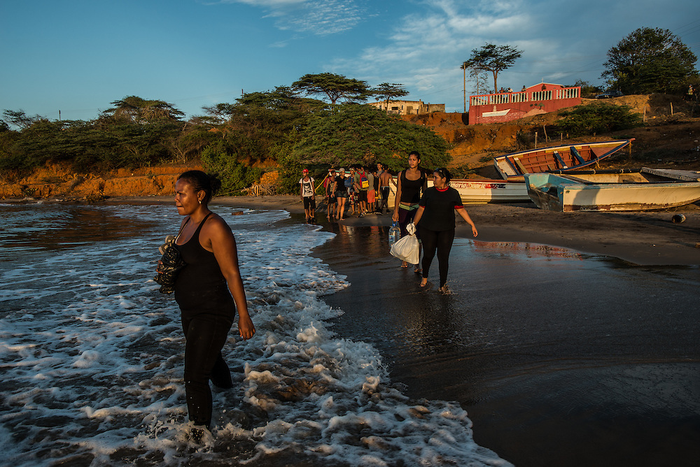 FALCÓN, VENEZUELA - SEPTEMBER 26, 2016: Undocumented migrants on the beach just before boarding the smuggler's boat that will illegally take them from Venezuela to Curaçao. Undocumented migrants here have mortgaged property, sold kitchen appliances and even borrowed money from the same smuggling rings that pack them on the floorboards alongside drugs and other contraband. The journey to Curaçao takes them on a 60-mile crossing filled with backbreaking swells, gangs of armed boatmen and coast guard vessels looking to capture migrants and send them home. Then, after being tossed overboard and left to swim ashore, they hide in the brush to meet contacts who spirit them anew into the tourist economy of this Caribbean island. They clean the floors of restaurants, work in construction, sell trinkets on the street, or even solicit Dutch tourists for sex. But at least, the migrants say, there is food. PHOTO: Meridith Kohut for The New York Times