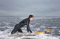 Surfer holding surfboard in water side view
