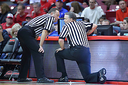 22 December 2013:  Referees Mark Whitehead and Mike Stuart chat at the replay screen during an NCAA  mens basketball game between the Blue Demons of DePaul falling to  the Illinois State Redbirds 69-64 in Redbird Arena, Normal IL