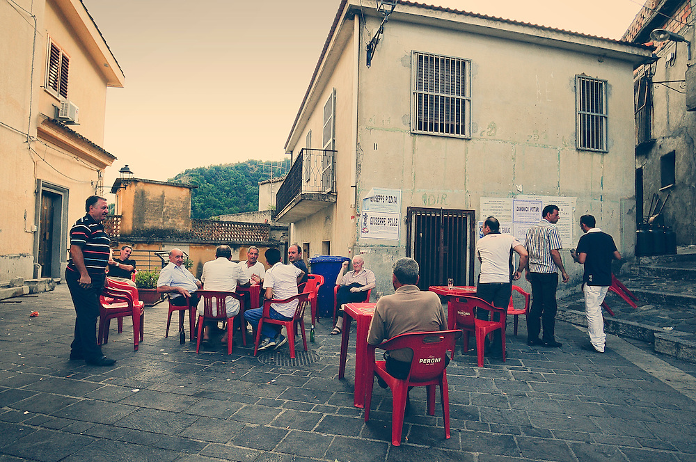 """San Luca (Reggio Calabria). Elderly people play cards out of the village's church. In August 2007 San Luca is back in the spotlight for the feud between the gangs Nirta-Strangio and Pelle-Vottari, after the """"Massacre of August"""" in the Italian restaurant Da Bruno in Duisburg (Germany) where six people were killed. Shortly after the massacre in Duisburg, San Luca has tried to present itself to the international press as a country forgotten by the world, full of lumberjacks unemployed, God-fearing women and a brave priest who fights tirelessly against the Mafia."""