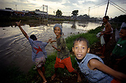Children Playing in a polluted river in the centre of Jakarta These pictures of Jakarta were taken during the fall of President Suharto. The photos are from a larger study of work about the city itself. <br />