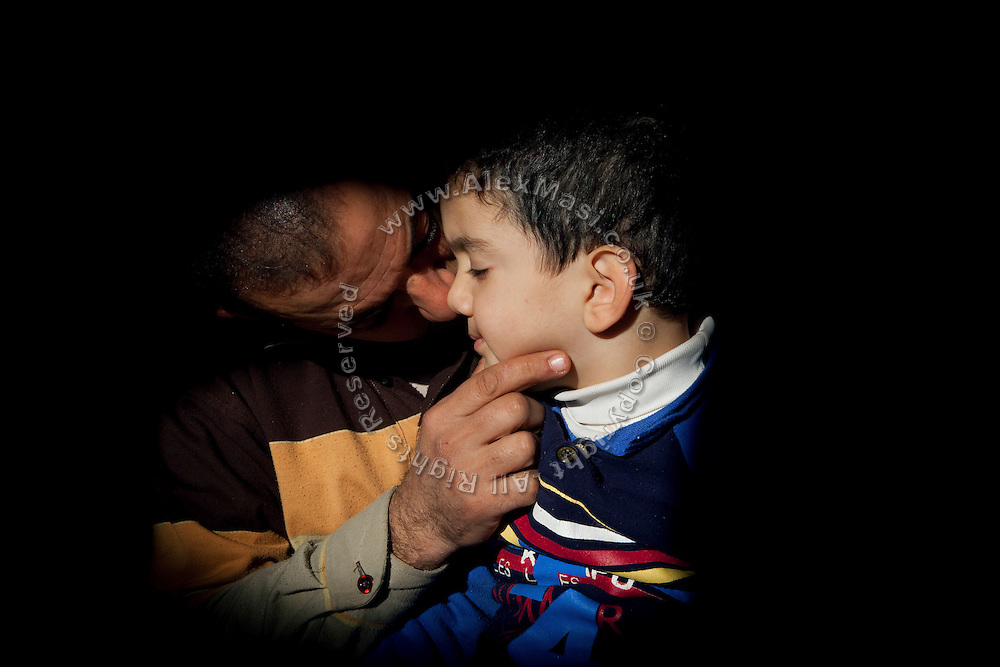 Yasir Ali, 32, is kissing Mustafah, 4, one of his three disabled children, while sitting on the floor of their home in Fallujah, Iraq. The parents and their relatives have no history of defects, and have been tested for compatibility.