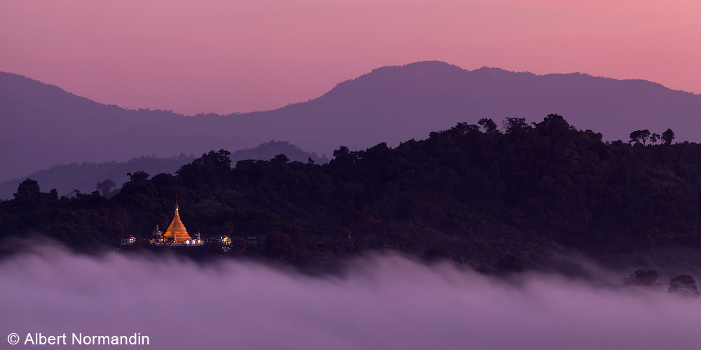Morning fog on Thandwe river with Golden Pagoda and mountains and pink sky