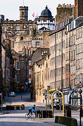 Edinburgh, Scotland, UK. 18 April 2020. Views of empty streets and members of the public outside on another Saturday during the coronavirus lockdown in Edinburgh. Cyclist on the Royal Mile. Iain Masterton/Alamy Live News