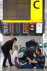© licensed to London News Pictures. London, UK 17/04/2014. A family waiting for their flight at Heathrow Airport terminal 5 in London on April 17, 2014 ahead of Easter holiday. Photo credit: Tolga Akmen/LNP