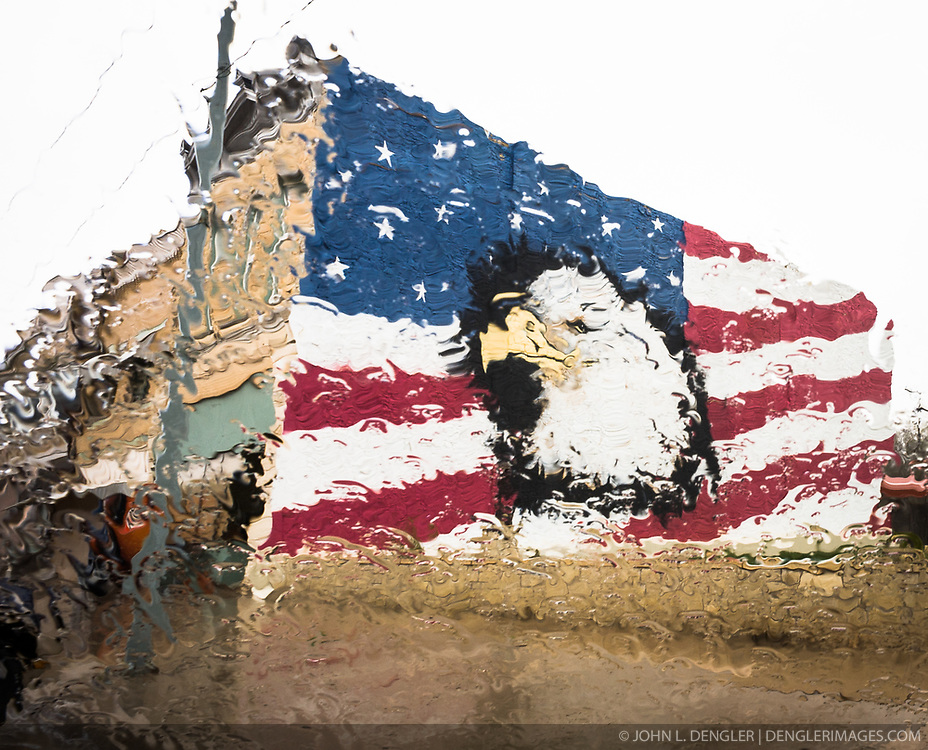 A patriotic mural of a bald eagle on a building in 400 Block of Main St. in Florence, Kansas takes on an impressionistic look when seen through a car windshield during rain. Florence is located in the Flint Hills in Marion County.