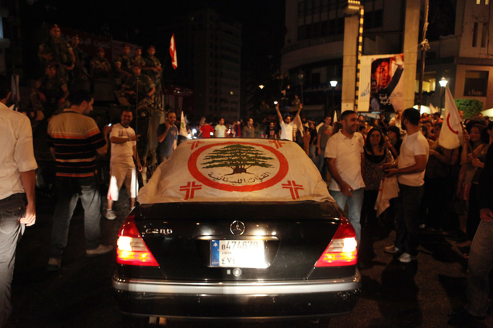 """As the results started to come out from Lebanon's general elections, the Beirut 1 district appeared to be swept by Christian groups from the pro-western """"March 14"""" alliance. As exit polls projected the win for March 14, supporters of the Lebanese Forces and Phalange parties came out to the Ashrafiyeh neighborhood's Sassine Square to celebrate. At around 1am Nadim Gemayel made a suprise appearance and briefly addressed supporters. Nadim Gemayel is the son of the Phalange party founder, Pierre Gemayel. Nadim's father, Bashir was assasinated in 1982 during the Lebanese civil war and remains one of the most popular icons of many of the Lebanon's Maronite Christians. The 27-year-old Nadim Gemayel will be one of Lebanon's youngest parliamentarians. The celebrations at Sassine were one of Lebanon's first celebrations after the elections ended on 7 June. ///A car draped in a Lebanese Forces flag drives through Sassine Square in Beirut."""