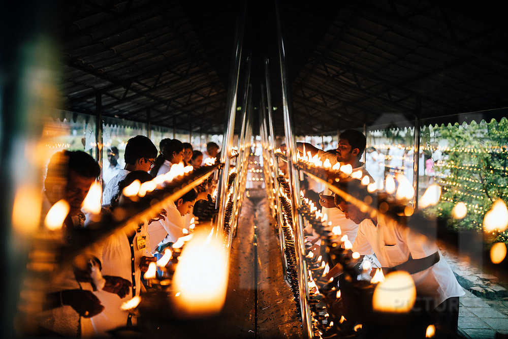 People gather and light candles at the Temple of the Tooth on Poya Day, Kandy, Sri Lanka, Asia