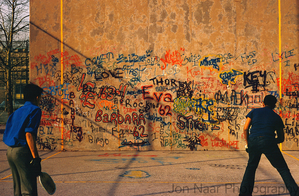 Two paddle ball players playing against a graffiti covered wall showing the first use of 'bubble letters'. by Eva 62 and Barbara 62. Nikon FM-2 with Kodachrome film. First published in Faith of Graffiti (1974).