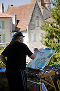 Artist painting town of Bourdeilles popular tourist destination near Brantome in Northern Dordogne, France