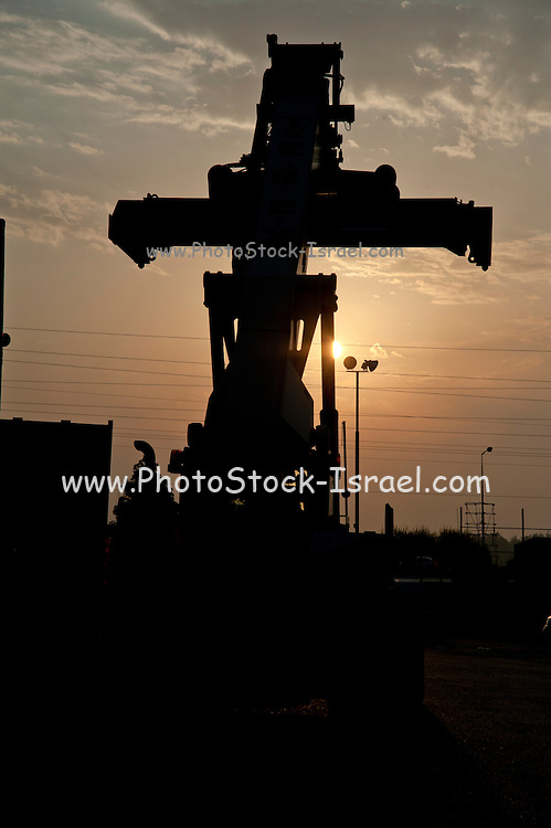 Shipping containers and forklift at a port awaiting export at sunset