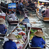 "According to ""Wikipedia"" - Damnoen Saduak Floating Market consists of a maze of narrow khlongs (canals), and can be navigated by boat. Female traders, often wearing traditional mo hom apparel (blue farmers' shirts) with wide-brimmed straw hats (ngob) use sampans (small wooden boats) to sell their wares, often produce that comes directly from farms. These boats are often full of vegetables and colorful fruits that are photogenic, and these images are used for tourism promotion. The market is often the busiest in the morning around 7 am to 9 am, and is active until noon."