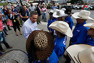 Ohio Governor John Kasich talks with members of the Ohio junior high rodeo team Wednesday, June 24, 2015, before going in for a quick look at the action inside the National Junior High Finals Rodeo at the Iowa State Fair Grounds in Des Moines, Iowa.
