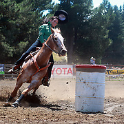 A cowgirl in action during the Barrel Race competition at the Millers Flat Rodeo. Otago, New Zealand. 26th December 2011