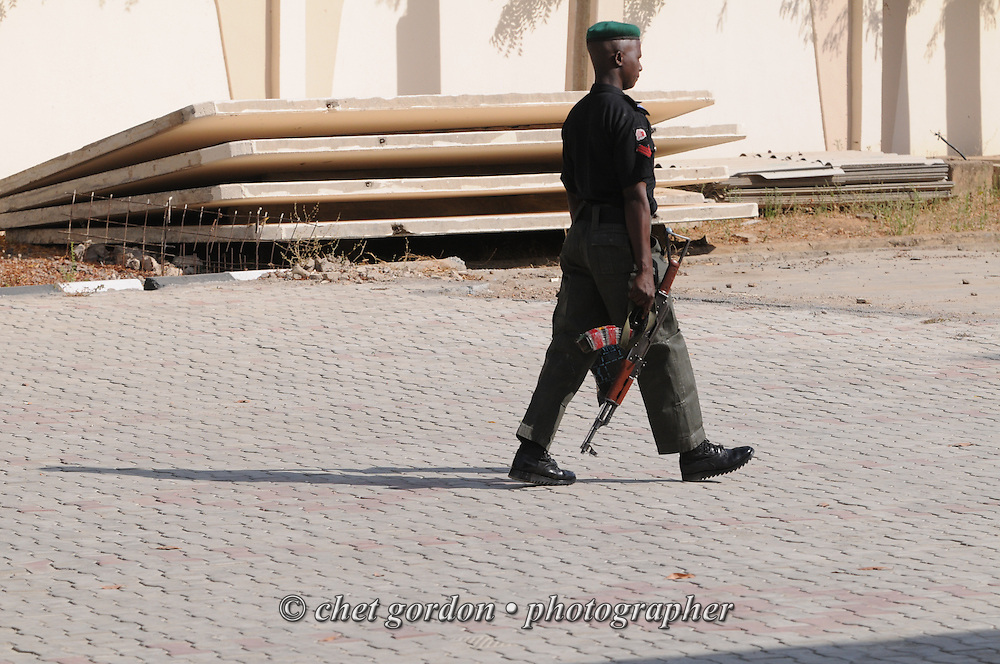 KANO, NIGERIA.  A Nigerian policeman patrols the grounds of Government House in Kano, Nigeria on Sunday, December 2, 2012. A police officer directing traffic was killed the following day when a roadside bomb exploded near his intersection in Kano.    © www.chetgordon.com