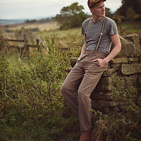 Portrait of young man sitting on a stone wall in a field