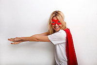 Side view portrait of happy woman in superhero costume against white background