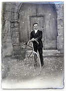 eroding glass plate with adult man posing with his bicycle