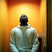 Frank who makes regular long distance call to his family in Ghana in a phone booth of a Long distance call shop, Hackney, London