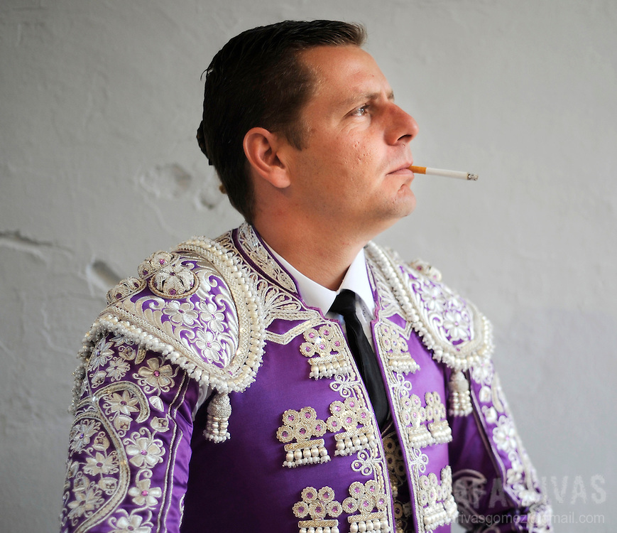 An assistant bullfighter smokes a cigarrette as he waits to take part in the third corrida of the San Fermin festivities, in the Spanish city of Pamplona, on July 10, 2008.