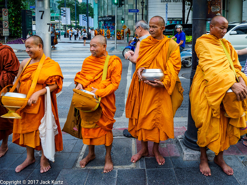 09 NOVEMBER 2017 - BANGKOK, THAILAND: Buddhist monks wait for people to give them alms in front of the Erawan Shrine on the 61st anniversary of the shrine's dedication. The Erawan Shrine is one of the most popular shrines in Bangkok. It was dedicated on November 9, 1956, after a series of construction accidents at what was then the Erawan Hotel (since torn down and replaced by the Grand Hyatt Erawan Hotel). The statue in the shrine is Phra Phrom, the Thai representation of the Hindu god of creation Brahma. It is a Hindu shrine popular with Thai and Chinese Buddhists because it is thought that making an offering to the Phra Phrom will bring good fortune.    PHOTO BY JACK KURTZ