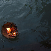 A diyaa, or ceremonial lamp, burns as it floats down the Ganges River during Ganga Aarti in Rishikesh, Uttarakhand, India.