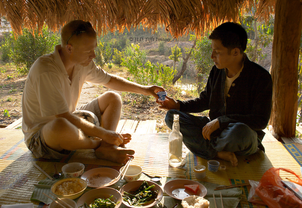 Two young men, an Australian and a Laotian, share a cup of village-mnade whisky after lunch.  They sit on a straw mat under a straw-roofed platform.