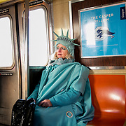 """QUEENS, NY - FEBRUARY 6, 2017: Lindley Hanlon rides the A train leaving John F Kennedy International Airport, where she dressed as the Statue of Liberty to welcome people entering through Terminal 4 in Queens, New York. While at the airport, law enforcement approached Hanlon and made her put away a sign that read """"Liberty and Justice for All."""" Hanlon made her costume from Bed Bath and Beyond curtains and purchased the crown from a Halloween store in the East Village. """"I think it's more important than ever,"""" she said about the Statue of Liberty. """"Because I think our liberties are threatened."""" CREDIT: Sam Hodgson for The New York Times"""