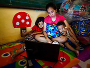 28 JANUARY 2018 - LEGAZPI, ALBAY, PHILIPPINES: HAZEL BERMUNDO (center) watches a movie on her laptop with her niece, TRISHA MAE AMARILLE, 6, (left) and nephew, DAVE AMARILLE, 2, at the evacuation shelter for people from Barangay (community) Matanag in Albay Central School in Legazpi. People from the community have been in the shelter since Mayon volcano started erupting two weeks ago. There are about 500 families at the shelter, around 2,000 people. More than 80,000 people have been evacuated from communities around the volcano and are living in shelters and camps outside of the evacuation zone. The Philippine government is preparing to house the people for up to three months.      PHOTO BY JACK KURTZ
