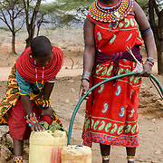 A Samburu mother and daughter fill water jugs at a local water tap in their village, Kiltamany,  outside of Samburu National Reserve, Kenya. Actress Drew Barrymore visited the tap in 2011.