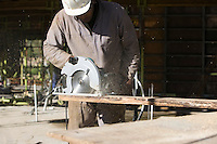 Workman cuts a plank with a circular saw